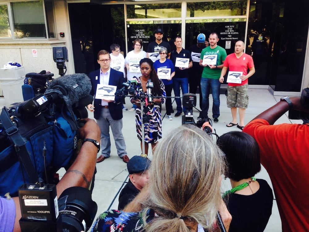 Equality NC's Crystal Richardson, center at microphones, speaks to media after Tillis and Berger ask for oral arguments.